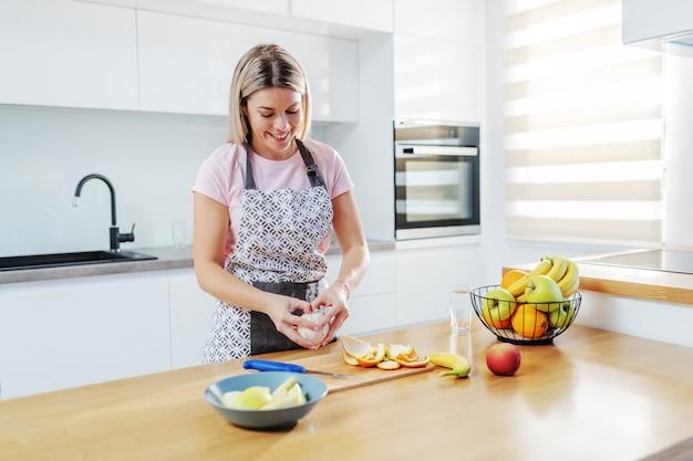 Uroczy Uśmiechnięty Pozytywny Kaukaski Blond Gospodyni Domowa W Fartuch Stojący W Kuchni I Obieranie Pomarańczy. Na Kuchennym Blacie Są Owoce. Premium Zdjęcia