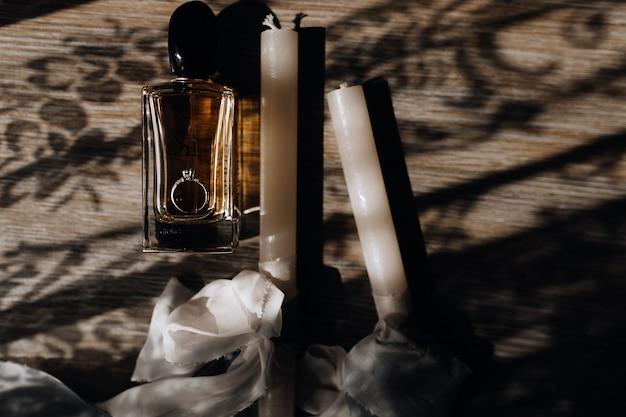 Uroczyste świece ślubne Z Białymi Wstążkami, Pierścionkiem Zaręczynowym I Perfumami Na Drewnianej Podłodze Darmowe Zdjęcia