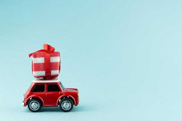 Uroczysty Boże Narodzenie Kartkę Z życzeniami Z Czerwonym Autko Przewożące Pudełko Na Niebiesko Premium Zdjęcia