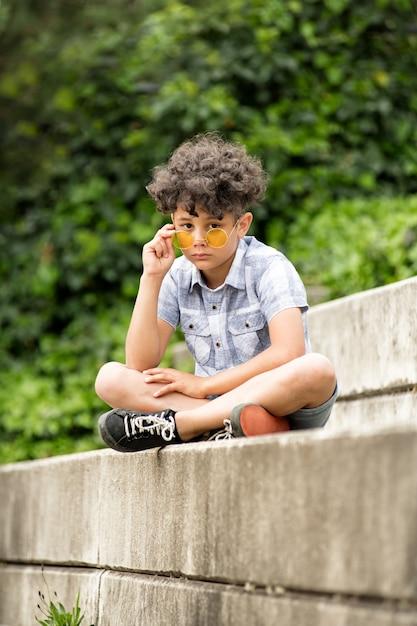 Uroczysty Mały Chłopiec W żółtych Okularach Przeciwsłonecznych Premium Zdjęcia