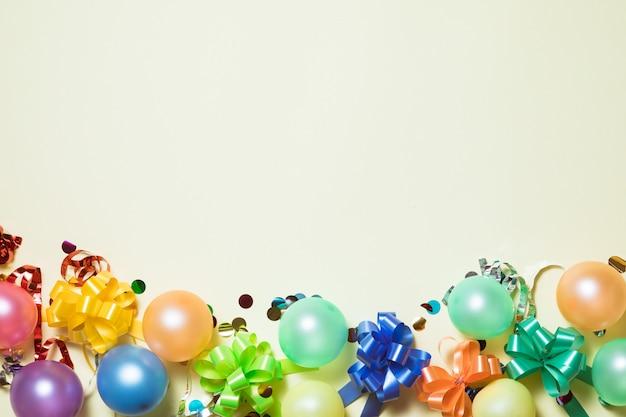 Urodziny jasne tło pastelowe z serpentyny, konfetti, balony na żółtym backround. Premium Zdjęcia