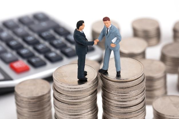 Uścisk dłoni dwóch biznesmenów na stosie monet Premium Zdjęcia