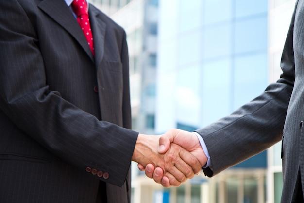 Uścisk dłoni na tle budynków Premium Zdjęcia