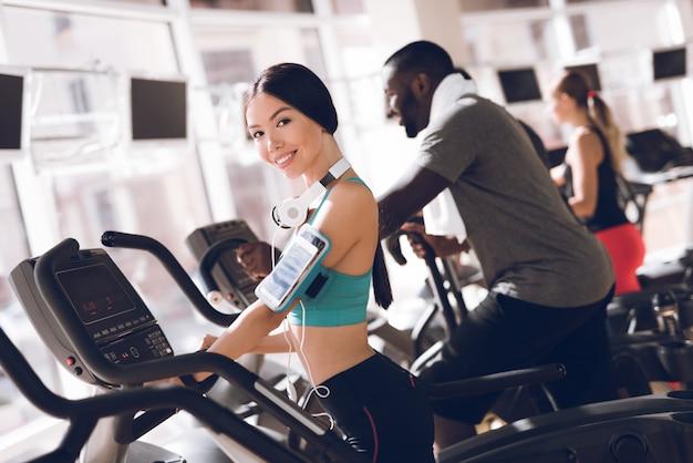 Uśmiech dziewczyna w siłowni koncentruje się na bieganie Premium Zdjęcia
