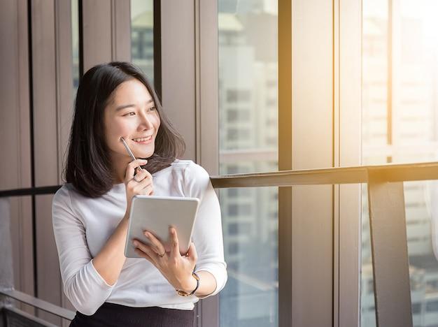Uśmiecha Się Biznesowej Kobiety Myśleć Z Pastylką W Nowożytnym Biurze Premium Zdjęcia