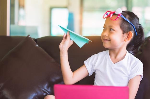 Uśmiecha Się Dziecko Dziewczyny Mienia Samolotu Papier Z Komputerem Dla Kreatywnie W Domu. Premium Zdjęcia