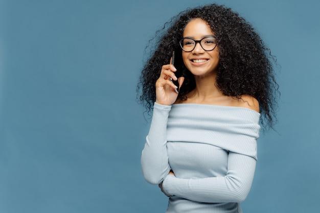 Uśmiechając Się Zachwycona Afro American Kobieta Z Kręconymi Włosami, Rozmawia Przez Inteligentny Telefon Premium Zdjęcia