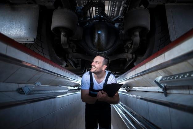 Uśmiechający Się Mechanicy Trzymając Laptop Narzędzie Diagnostyczne Pod Ciężarówką W Warsztacie Darmowe Zdjęcia