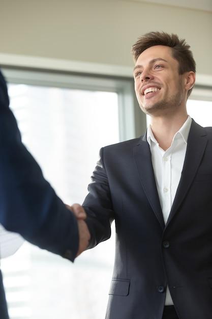 Uśmiechający się młody biznesmen sobie czarny garnitur drżenie ręki mężczyzna, Darmowe Zdjęcia
