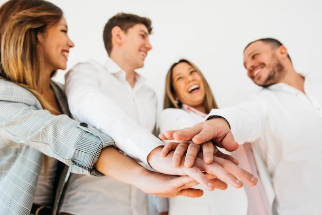 Uśmiechający się współpracowników biura kładąc ręce razem Darmowe Zdjęcia