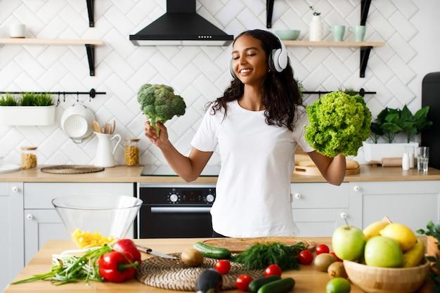 Uśmiechana Mulatowa Kobieta W Dużych Bezprzewodowych Słuchawkach Uśmiecha Się I Trzyma Sałatkę I Brokuły Na Nowoczesnej Kuchni Przy Stole Pełnym Warzyw I Owoców Darmowe Zdjęcia