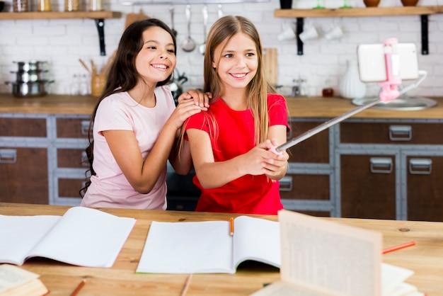 Uśmiechnięci Dzieci Siedzi Przy Biurkiem I Bierze Selfie Przy Kuchnią Darmowe Zdjęcia