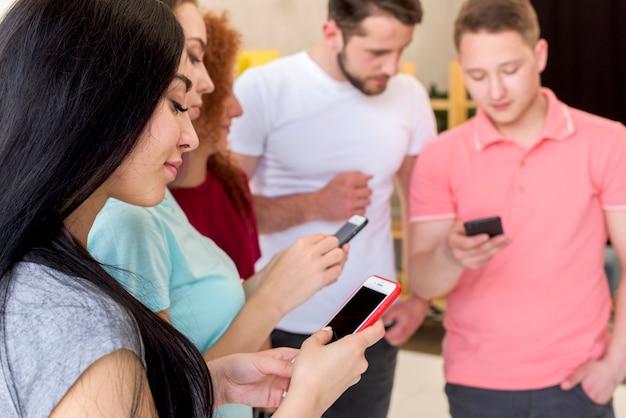 Uśmiechnięci mężczyźni i kobiety korzystający z telefonów komórkowych Darmowe Zdjęcia