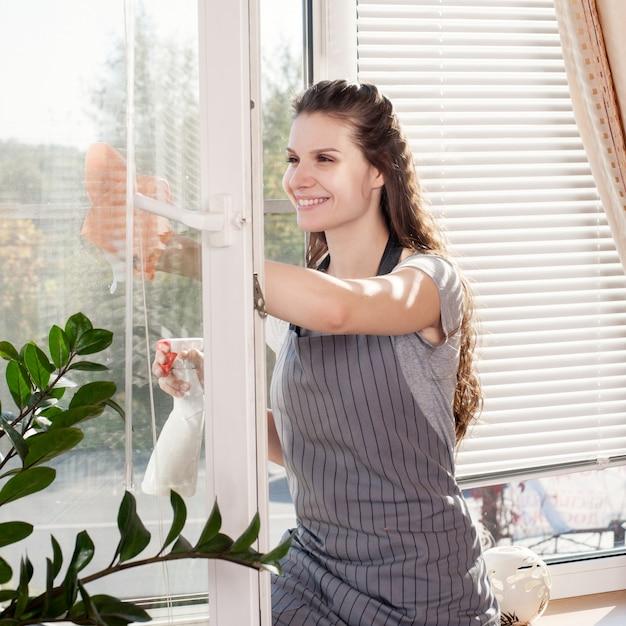 Uśmiechnięci młodzi brunetki cleaning okno używać atomizatora salowego Premium Zdjęcia