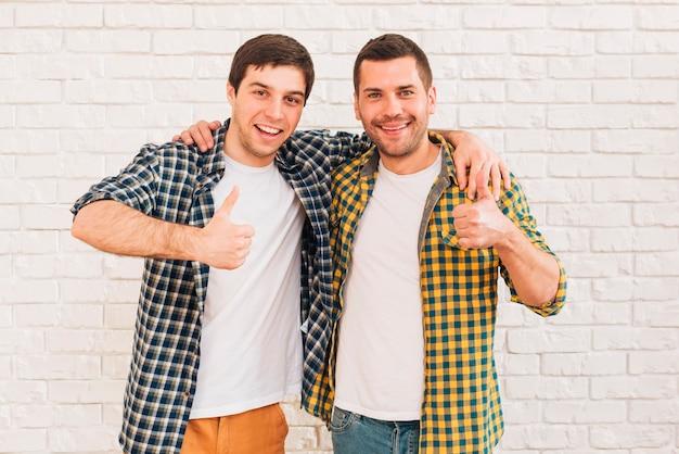 Uśmiechnięci młodzi człowiecy z ich rękami wokoło ich ramienia pokazuje kciuk up podpisują Darmowe Zdjęcia