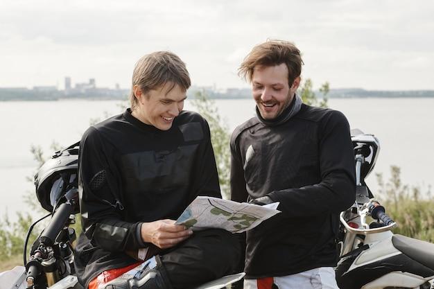 Uśmiechnięci Młodzi Mężczyźni W Kamizelkach Motocyklowych Stojąc Nad Jeziorem I Używając Mapy Przy Wyborze Trasy Motocyklowej Premium Zdjęcia