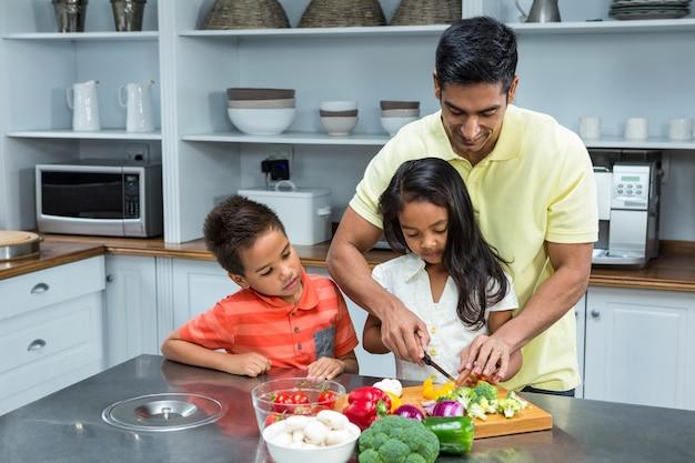 Uśmiechnięci Ojca Przecinania Warzywa Z Jego Dziećmi Premium Zdjęcia