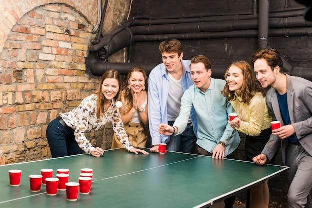 Uśmiechnięci przyjaciele bawić się piwnego pong na stole w barze Darmowe Zdjęcia