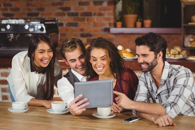Uśmiechnięci Przyjaciele Patrzeje Cyfrową Pastylkę Premium Zdjęcia