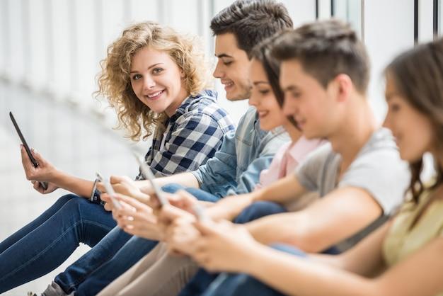 Uśmiechnięci przyjaciele siedzą na podłodze i oglądają zdjęcia. Premium Zdjęcia