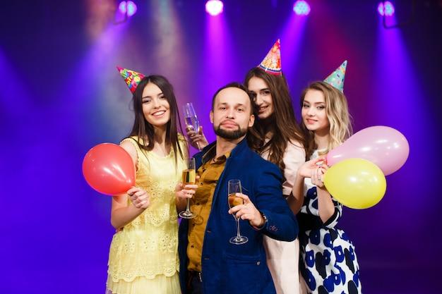 Uśmiechnięci przyjaciele z kieliszkami szampana w klubie Premium Zdjęcia