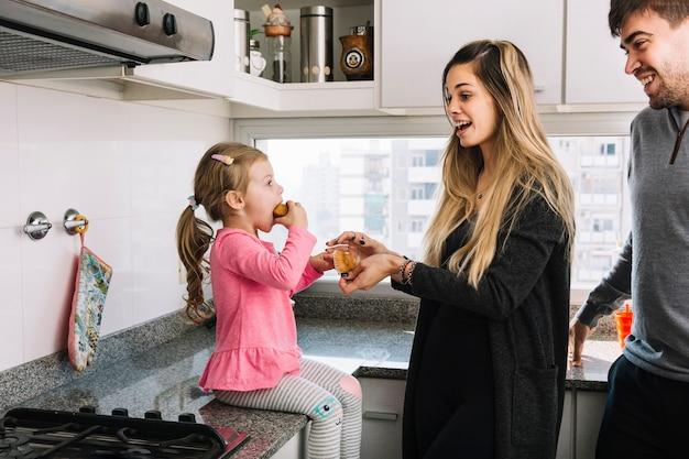 Uśmiechnięci Rodzice Patrzeje Ich Córki łasowania Babeczkę W Kuchni Darmowe Zdjęcia