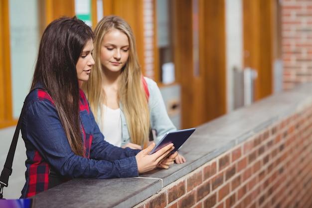 Uśmiechnięci Ucznie Używa Pastylkę Wpólnie Na Uniwersytecie Premium Zdjęcia
