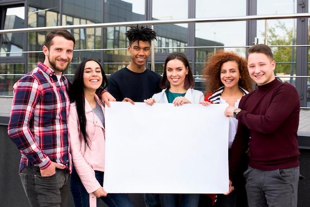Uśmiechnięci wieloetniczni ucznie trzyma pustą białą plakatową pozycję przed szklanym budynkiem Darmowe Zdjęcia