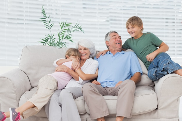Uśmiechnięci wnuki obejmuje ich dziadków Premium Zdjęcia