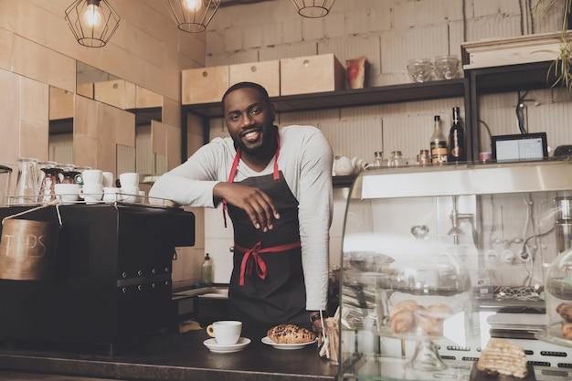 Uśmiechnięta afro amerykańska barista samiec przy pracą Premium Zdjęcia