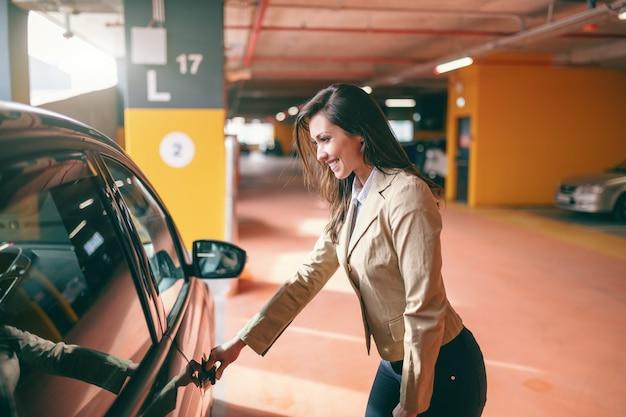 Uśmiechnięta Atrakcyjna Brunetka Ubierał Mądrze Przypadkowego Otwarcia Samochodowego Drzwi Przy Jawnym Garażem. Premium Zdjęcia