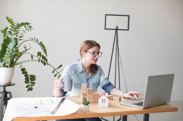 Uśmiechnięta atrakcyjna kobieta trzyma filiżankę podczas gdy pracujący na laptopie Darmowe Zdjęcia
