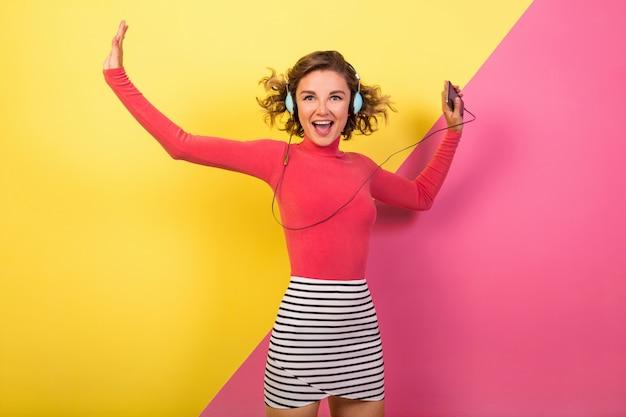 Uśmiechnięta Atrakcyjna Uśmiechnięta Podekscytowana Kobieta W Stylowym, Kolorowym Stroju, Taniec I Słuchanie Muzyki W Słuchawkach Na Różowym żółtym Tle, Trend Lato Moda Darmowe Zdjęcia