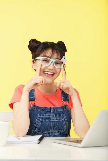 Uśmiechnięta azjatycka dziewczyna z topknots, w jaskrawo coloured szkłach siedzi przy biurkiem z laptopem Darmowe Zdjęcia