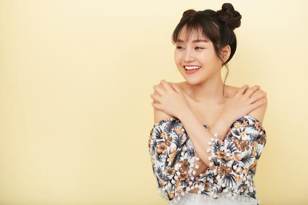 Uśmiechnięta azjatycka kobieta z rękami na ramionach pozuje i patrzeje na boku Darmowe Zdjęcia