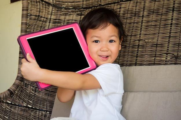 Uśmiechnięta Azjatycka Małej Dziewczynki Mienia Pastylka Na Ona Ręki. Pojęcie Czasu Szczęścia Z Technologią I Dzieckiem. Premium Zdjęcia