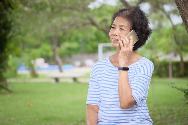 Uśmiechnięta Azjatykcia Starsza Kobieta Używa Smartphone Obsiadanie Przy Ogródem Premium Zdjęcia