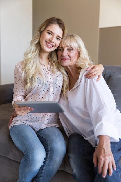 Uśmiechnięta Babcia I Jej Wnuczka Trzyma Pastylkę Darmowe Zdjęcia