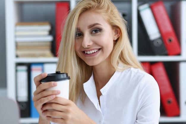Uśmiechnięta Biznesowa Kobieta Pije Kawę Od Papierowej Filiżanki W Biurowym Portrecie Patrzeje W Kamery Mienie W Jej Ręce I Odpoczywa Podczas Przerwy. Premium Zdjęcia