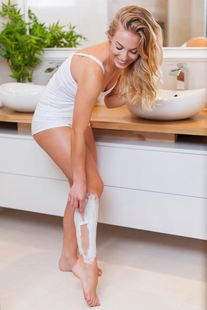 Uśmiechnięta Blondynka Golenia Nóg W łazience Darmowe Zdjęcia