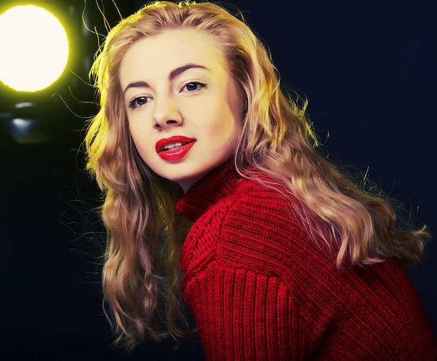 Uśmiechnięta blondynka w czerwonym swetrze Premium Zdjęcia