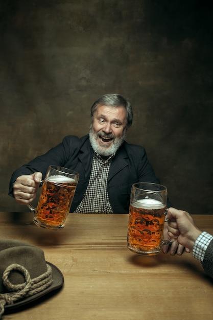 Uśmiechnięta Brodata Samiec Pije Piwo W Pubie Darmowe Zdjęcia