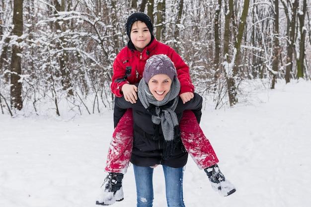 Uśmiechnięta chłopiec cieszy się prosiątko z jego matką w zimie przy lasem Darmowe Zdjęcia