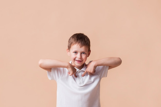 Uśmiechnięta chłopiec wskazuje palec wskazującego przy on stoi blisko beż ściany Darmowe Zdjęcia