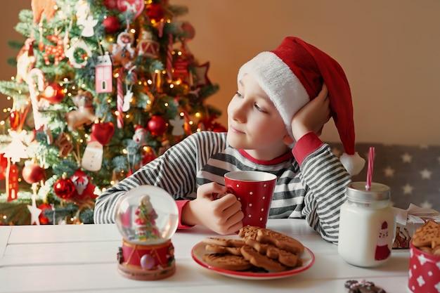 Uśmiechnięta Chłopiec Z Boże Narodzenie Czerwoną Filiżanką Herbata Przy Christmass Drzewem. Rodzina Z Dziećmi świętuje Ferie Zimowe. Wigilia W Domu. Chłopiec Dziecko W Boże Narodzenie Kuchni. Chłopiec W Santa Hat. Premium Zdjęcia