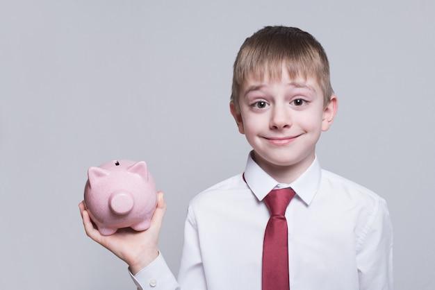 Uśmiechnięta chłopiec z różową prosiątko banka świnią w jego rękach. pomysł na biznes. Premium Zdjęcia