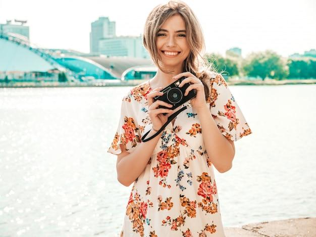 Uśmiechnięta Dziewczyna Hipster W Modną Letnią Sukienkę Trzymając Aparat Retro Darmowe Zdjęcia