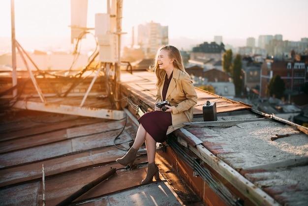 Uśmiechnięta Dziewczyna Na Dachu Z Kamerą Młoda Blondynka Pozuje Przy Zmierzchem Premium Zdjęcia