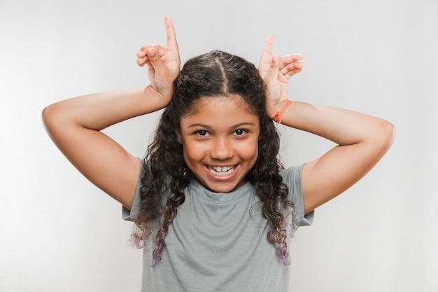 Uśmiechnięta Dziewczyna Robi Róg Gestowi Przeciw Białemu Tłu Darmowe Zdjęcia