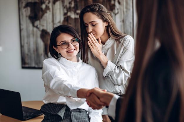 Uśmiechnięta Dziewczyna W Okularach Podaje Rękę Do Kolegi, Podczas Gdy Jej Asystent Mówi Coś Do Jej Ucha Premium Zdjęcia